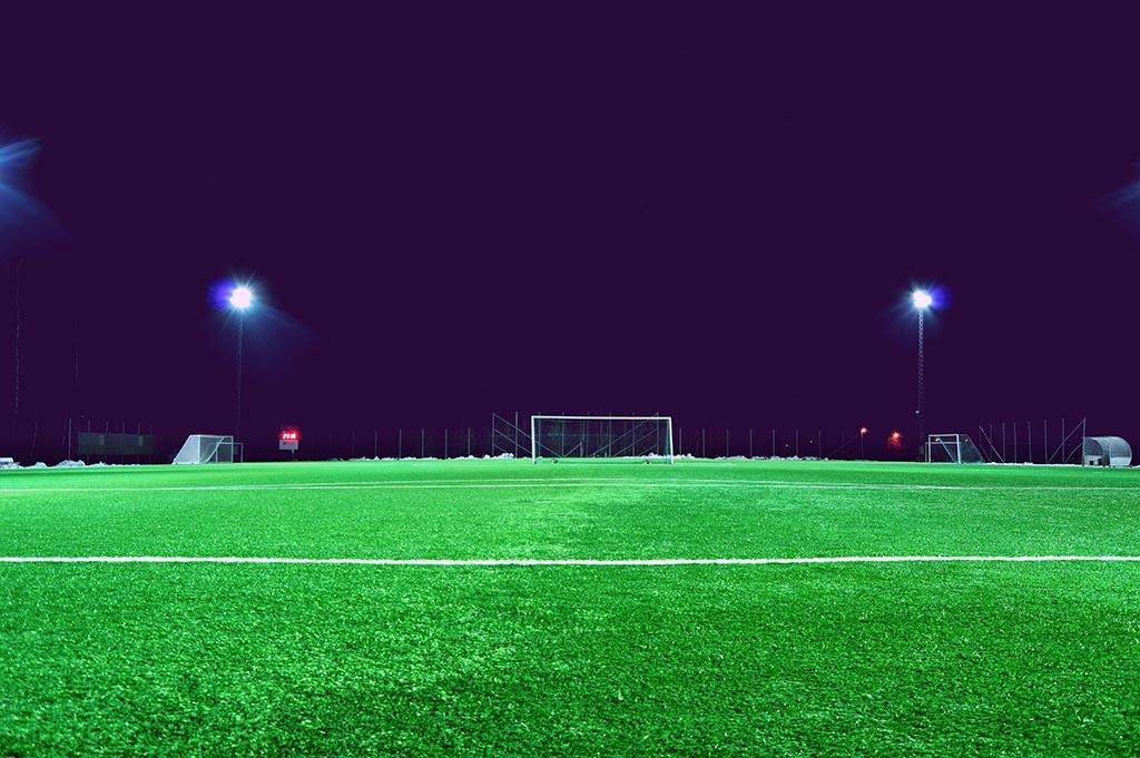 En belyst fotbollsplan en mörk kväll. Symbolik: SteadyGo jobbar med sportkommunikation.